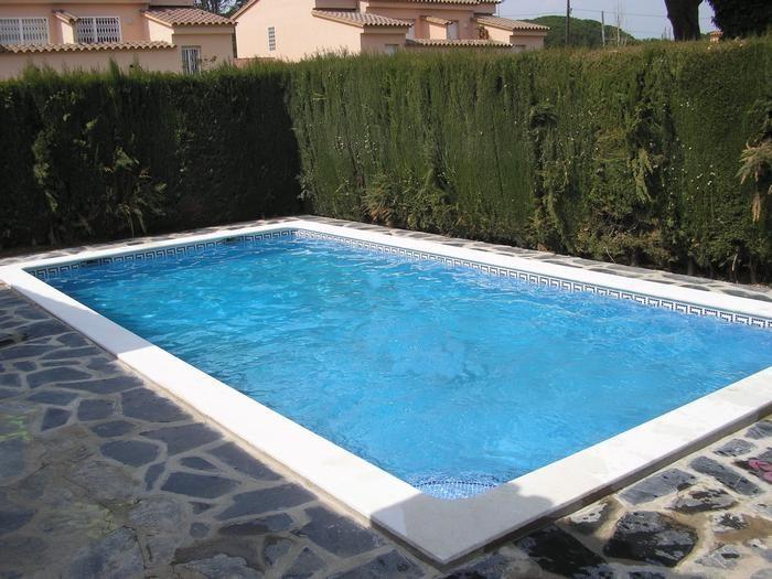 Grande piscine privée avec terrasse meublée.