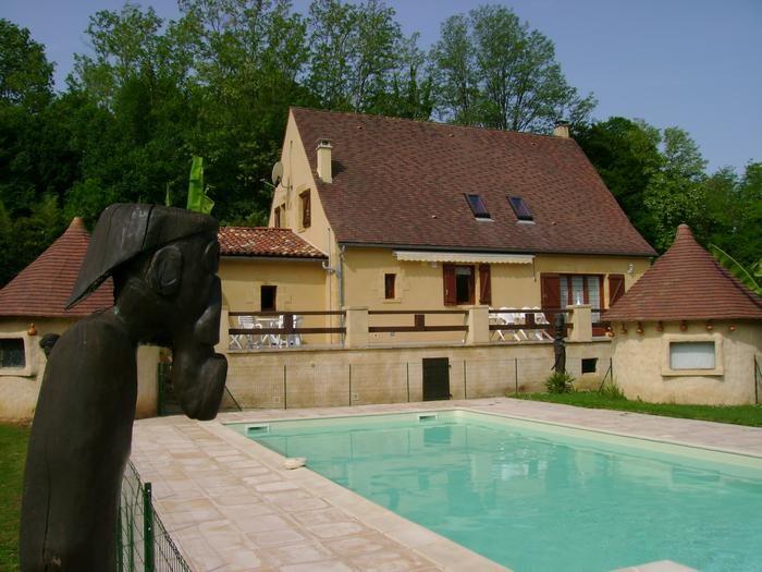 Une maison avec terrasse surplombant la piscine pour une vue sur le bain.
