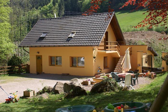 Maison dans un jardin clôturé, vu sur un étang