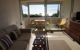La pièce à vivre avec un coin salon et un coin repas, qui ouvre sur la terrasse.