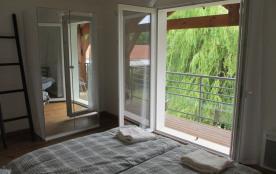 """""""Matisse"""" Chambre 1 avec grand armoire. Accès au balcon sud et vue sur le jard"""