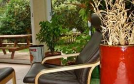 Véranda avec grande table et 6 chaises plus 2 banquettes et 2 fauteuils cuir