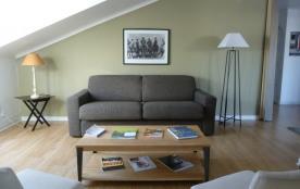 Salon avec canapé lit confortable et rideaux occultants