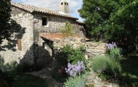 Maison en pierre au cœur d'un petit hameau de moyenne montagne, blotti au pied d'un rocher de bas...