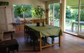 Véranda ensoleillée équipée d'une table de repas et d'un salon : 2 canapés+faut