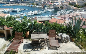 Terrasse vue mer avec table, chaises et deux transats