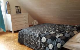 Chambre de l'étage avec lit double et lit bébé en bois.