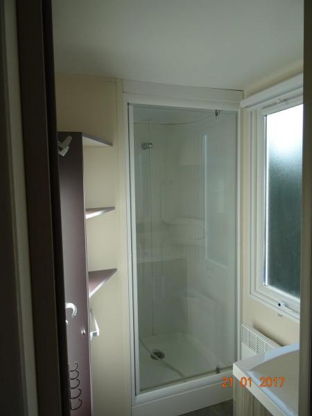 salle d'eau avec meuble de rangement sous vasque et grande douche