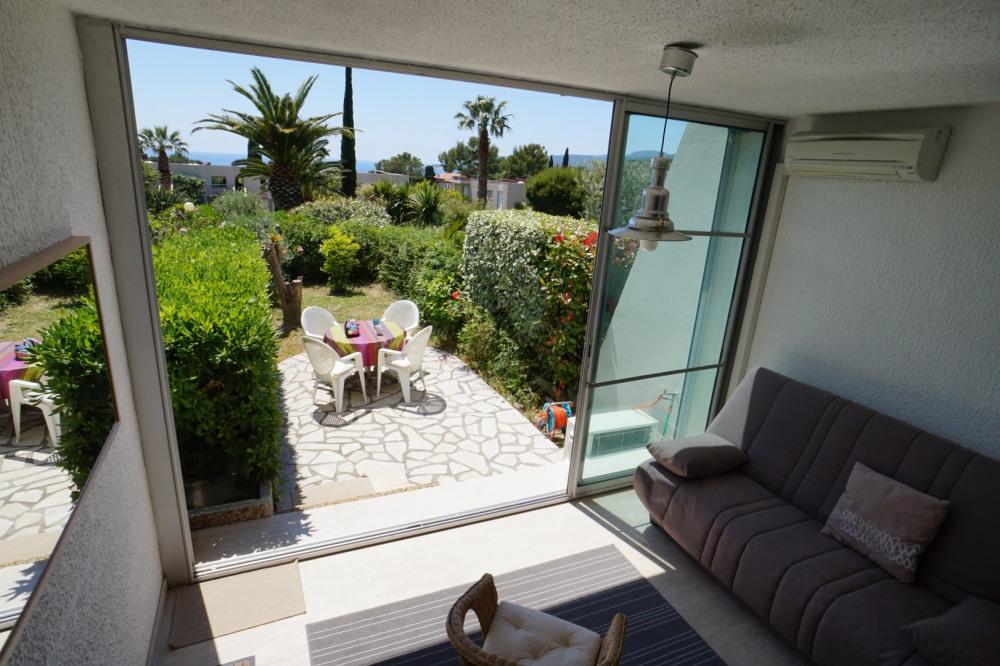 La loggia ouvre sur le jardin clos, avec terrasse, entouré de haies taillées.