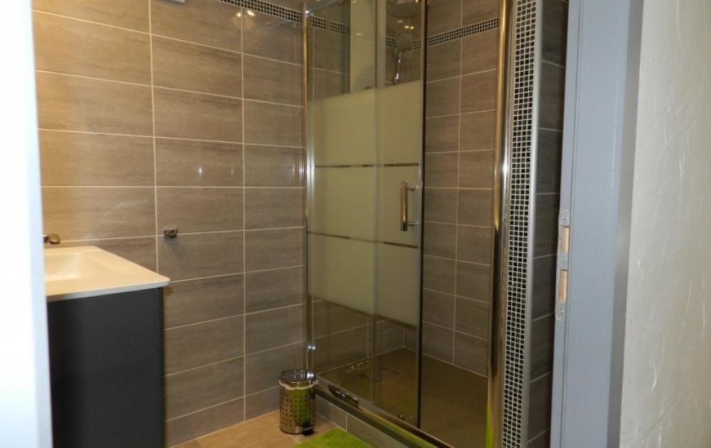 salle de bains avec vasque,  douche, et rangements