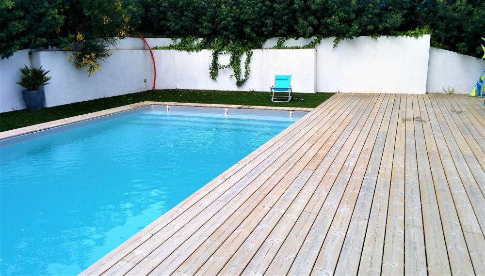 Terrasse en bois jouxtant la piscine