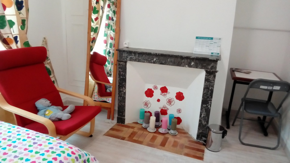 Paet of the room with a chair, reading table and chair