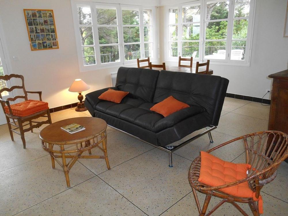 Côté salon avec fenêtres et baie vitrée donnant sur terrasse et vue mer