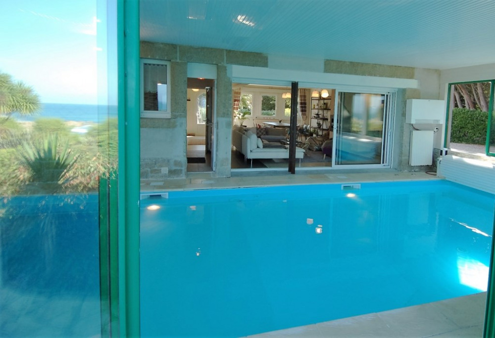 piscine intérieure avec salon dans le prolongement et salle de bain