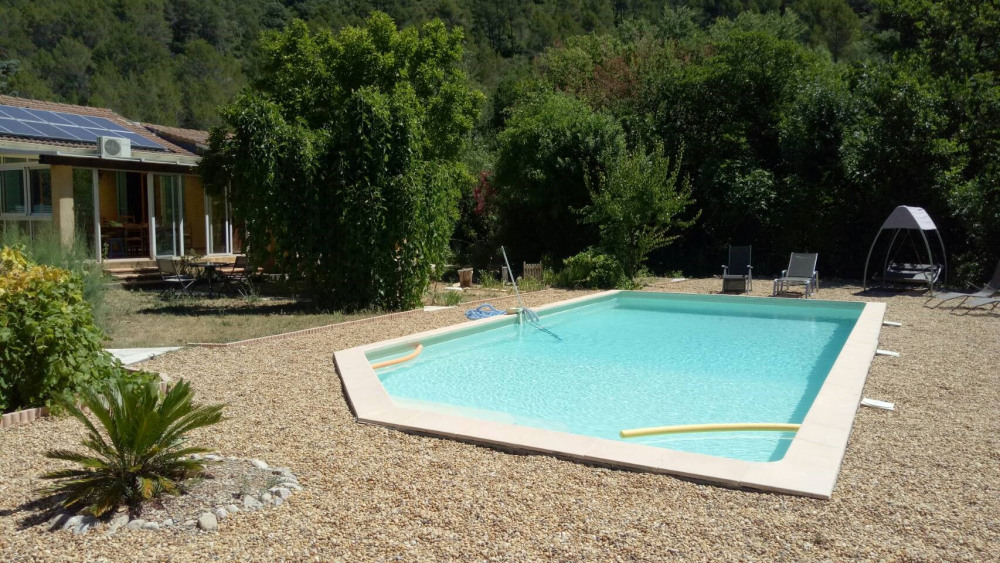 swimming pool and garden with chairs and balancelle
