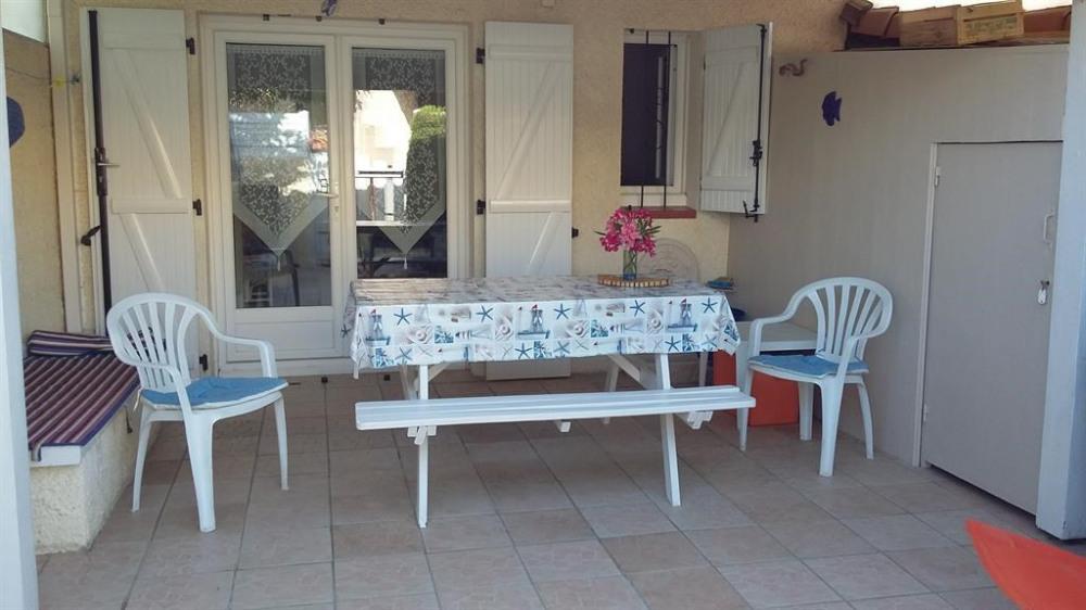 terrasse avec auvent en tuiles  barbecue et table