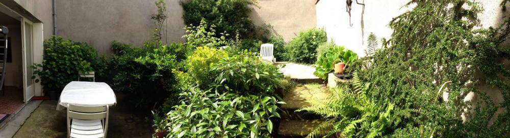 jardin clos et sécurisé avec table, chaises et chaises longues