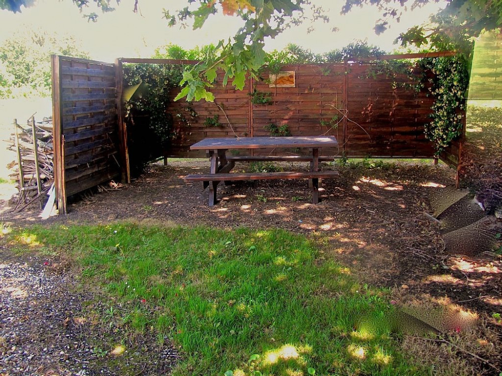 coin detente avec table et bancs en bois a l'ombre du grand chêne