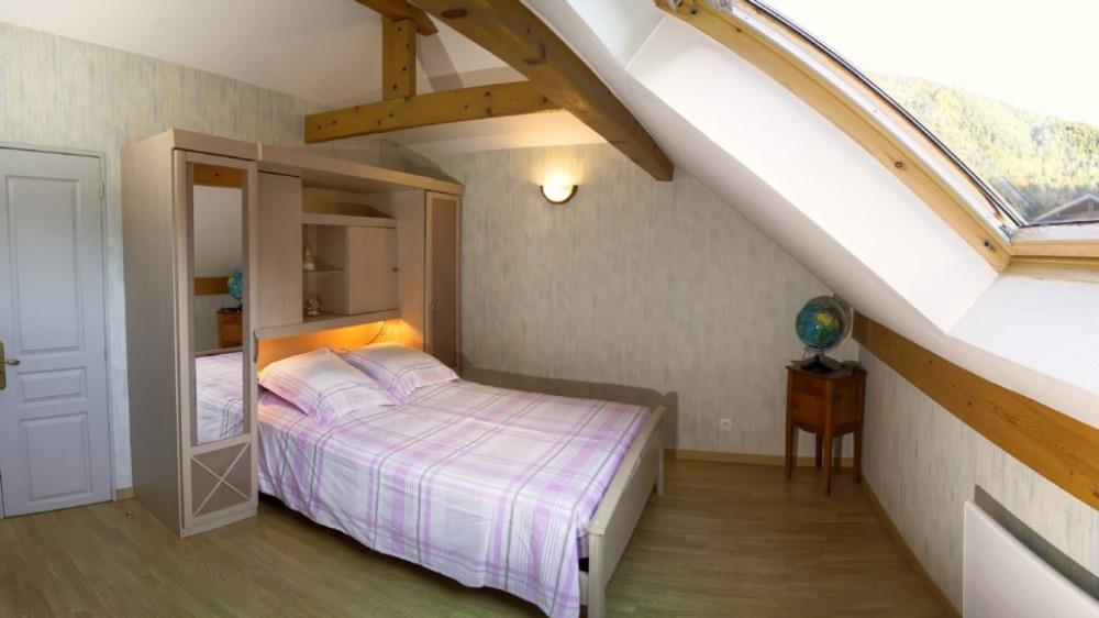 La chambre à coucher avec son lit 2 places et communicant avec la salle de ba...