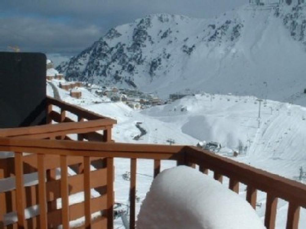 vue du balcon sur piste et village en hiver