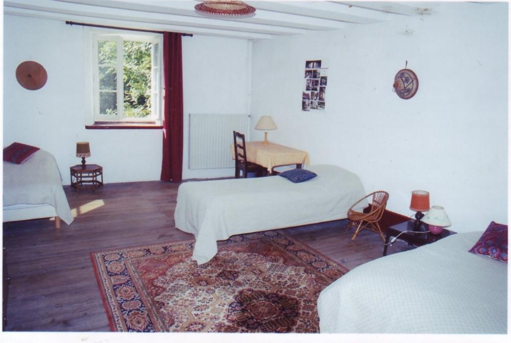 une grande chambre avec 3 lits