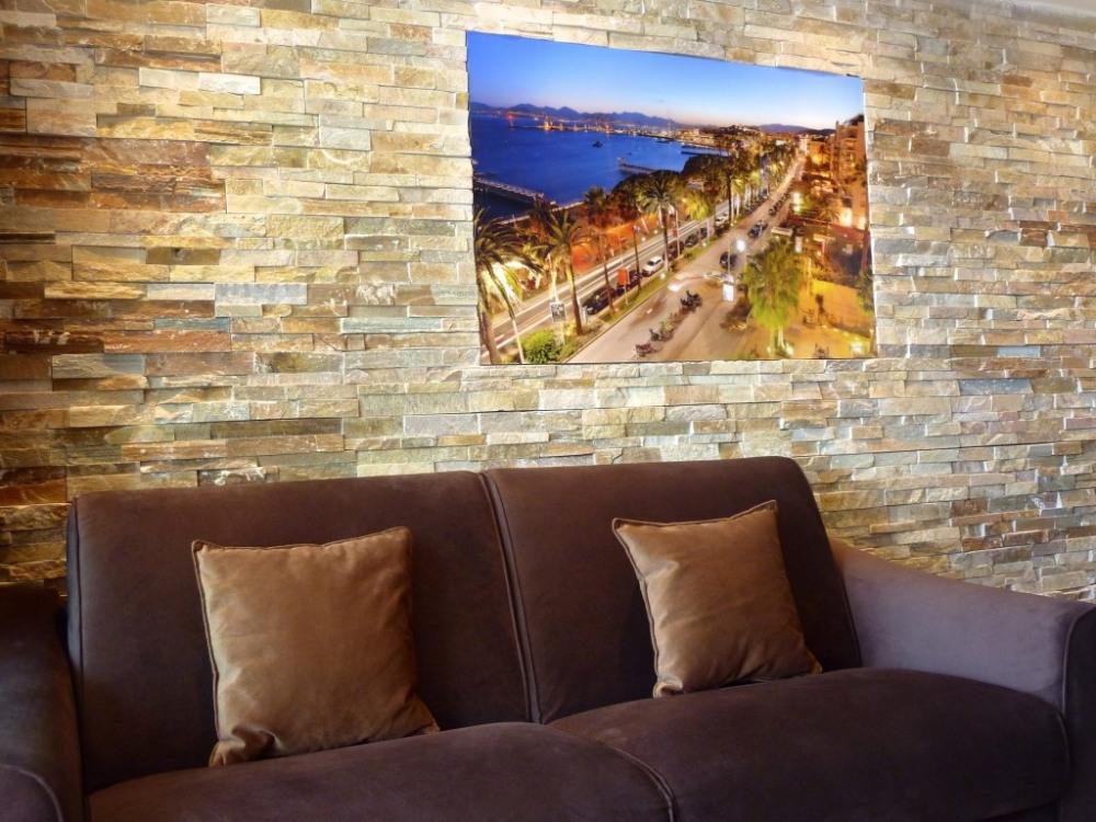 Salon décoré, mur en pierre naturelle, canapé haut de gamme esprit contempora...