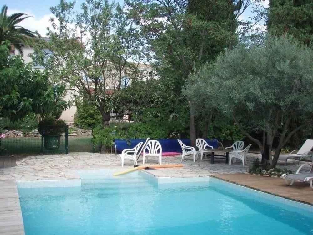Espace piscine avec salon et bains de soleil sous les oliviers