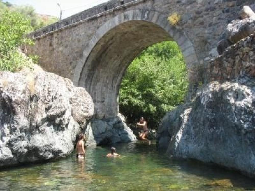 un torrent et un pont génois dans la montagne au dessus du lac