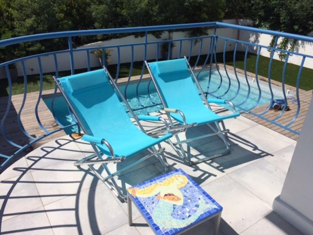 Petit balcon côté piscine éclairé par le coucher de soleil
