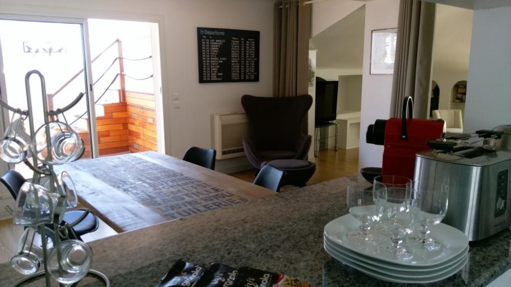 Vue de la cuisine ouverte sur la salle à manger et la terrasse