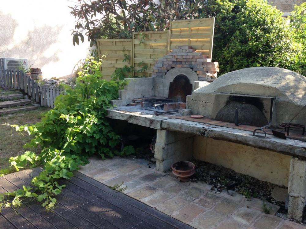 Barbecue et four à bois avec point d'eau et espace détente sous les canisses