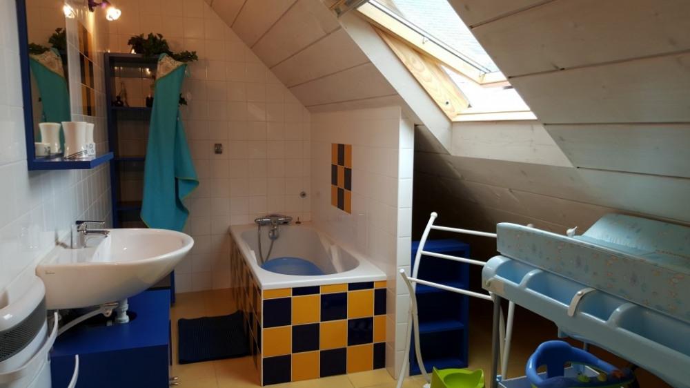 Salle de bains avec baignoire et table à langer