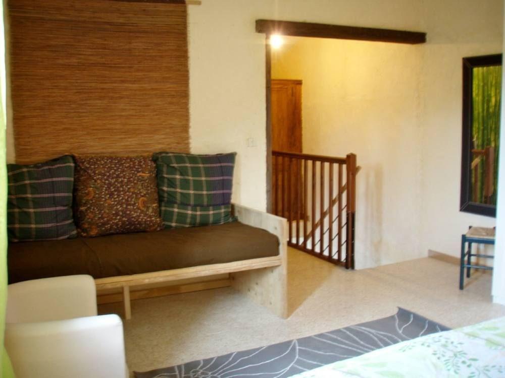 A l'étage, grande chambre avec banquette-lit, lit king size, salle d'eau et WC