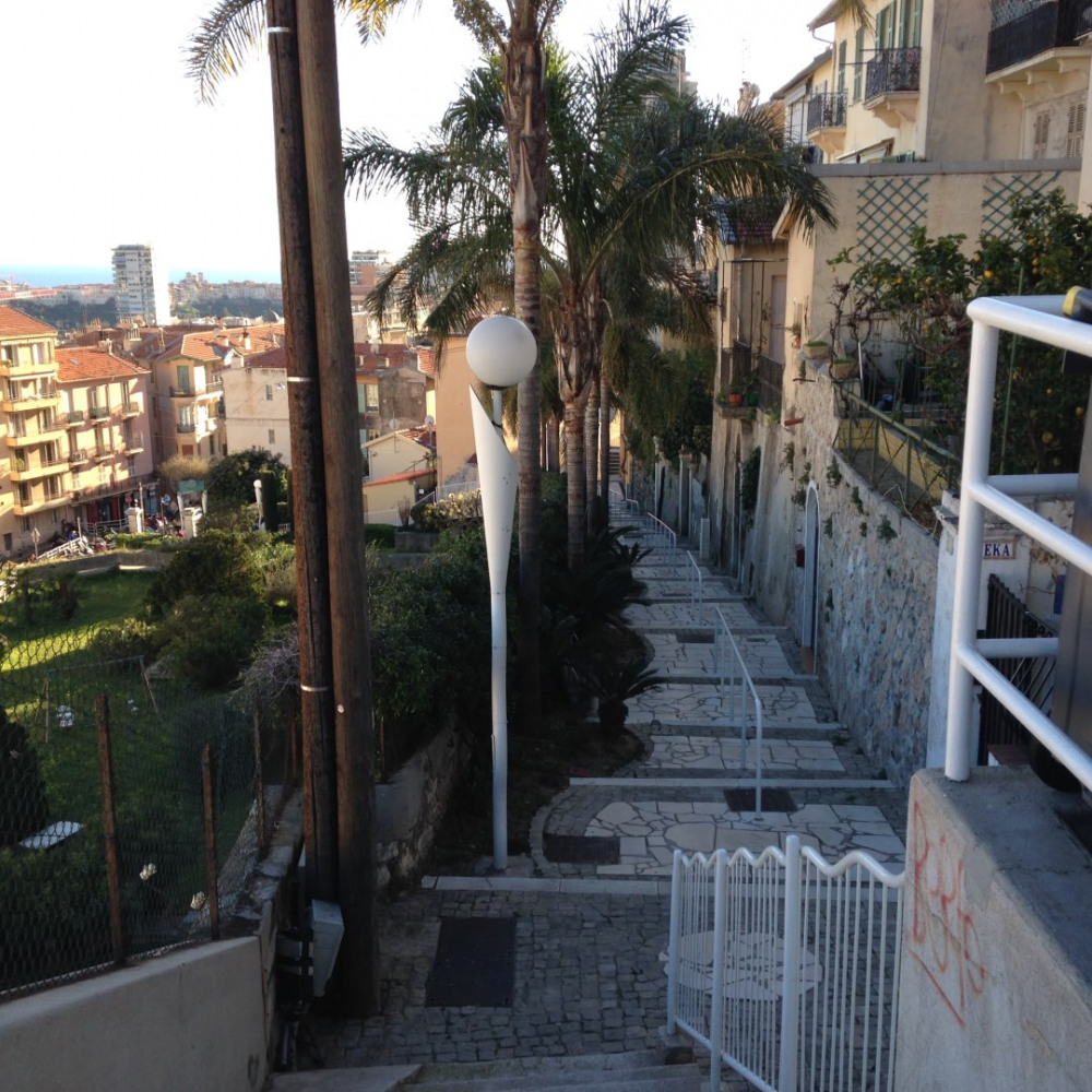 escalier à droite en sortant de la maison vers les bars restaurants parking
