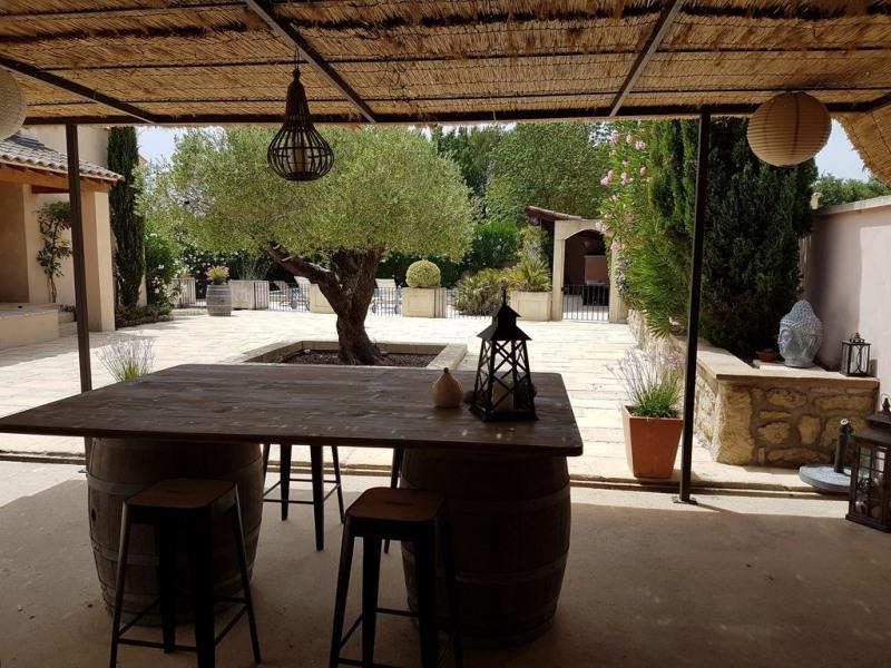 La terrasse avec en arrière plan l'olivier et la piscine clôturée