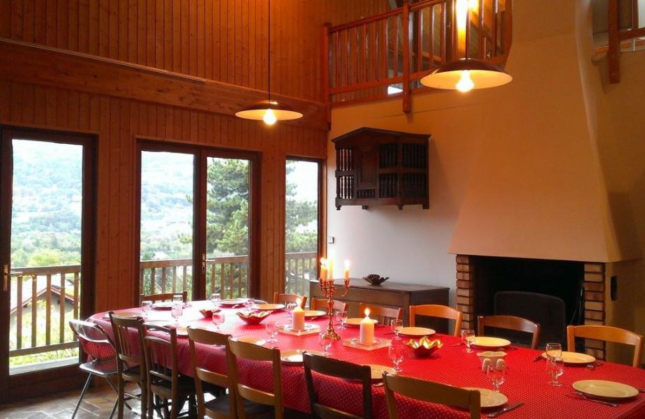 Grande salle-à-manger, table granit, cheminée, mobilier bois.
